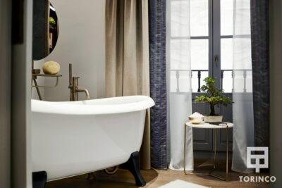 Bañera del baño del hotel junto a una ventana de aislamiento acústico y térmico