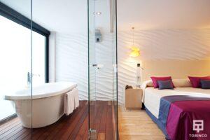 Bañera en la habitación del hotel al lado de una ventana de aislamiento acústico