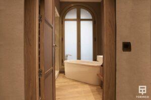 Bañera de una habitación del hotel al lado de una ventana de aislamiento acústico.