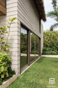 Parte lateral de la vivienda con ventanas de madera de aislamiento térmico y gran apertura