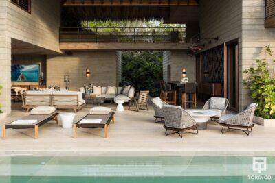 Zona de relax de la vivienda junto a la piscina con ventanas de madera de aislamiento térmico y gran apertura en los laterales